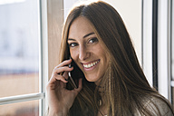 Portrait of smiling young woman on the phone at the window - KKAF00328