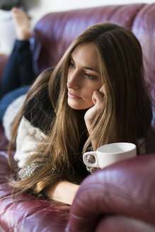 Young woman lying on couch with cup of coffee - KKAF00340