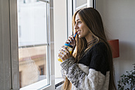Young woman at the window drinking homemade drink - KKAF00349