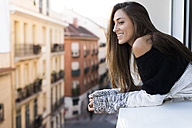 Smiling young woman leaning on window sill - KKAF00358
