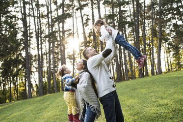 Playful family with two girls in forest - HAPF01300