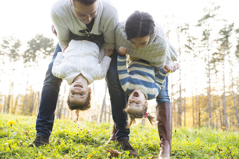 Playful family with two girls on meadow - HAPF01309