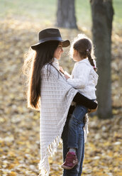 Mother carrying her daughter in autumnal forest - HAPF01312