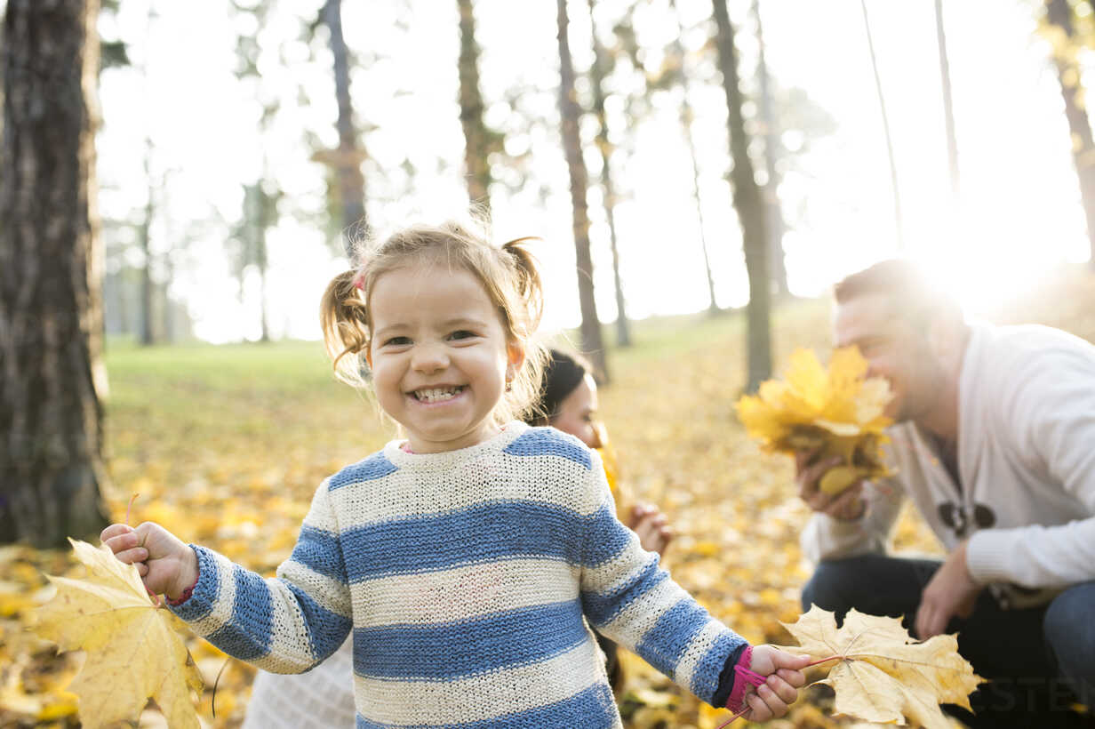 Happy girl with family in autumnal forest - HAPF01315 - HalfPoint/Westend61
