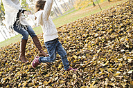 Girl running with mother in autumnal leaves - HAPF01318