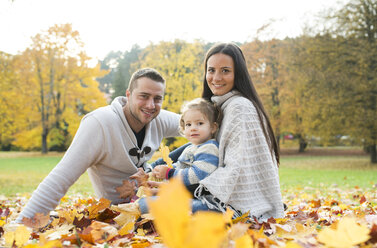 Happy family sitting in autumn leaves - HAPF01321