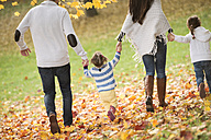 Happy family with two girls walking in autumn leaves - HAPF01324