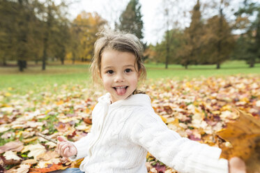 Portrait of playful girl in autumn leaves - HAPF01327