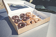 Doughnuts with different icings in a box on car bonnet - EPF00282