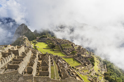 Peru, Andes, Urubamba Valley, Machu Picchu with mountain Huayna Picchu in fog and clouds - FOF08766