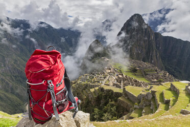 Peru, Andes, Urubamba Valley, red backpack at Machu Picchu with mountain Huayna Picchu - FOF08774