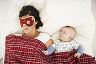 Mother with sleep mask and awake baby lying in bed - FSF00654