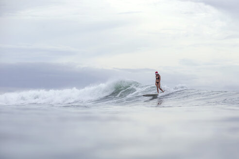 Indonesia, Bali, woman wearing Santa hat surfing on a wave - KNTF00622
