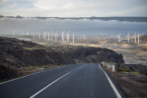 Spain, Tenerife, empty country road with wind wheels in the background - SIPF01343