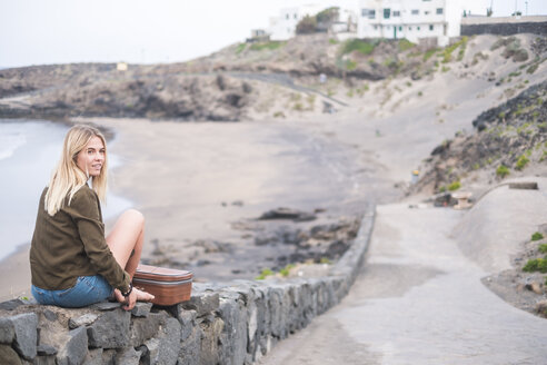 Spain, Tenerife, young blond woman sitting on wall near the beach - SIPF01346
