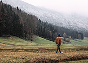 Austria, Mondsee, back view of young man strolling in autumn - WVF00807