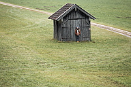Young man standing in front of wooden hut on a meadow - WVF00813