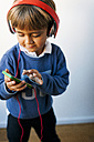 Little boy listening to music of his smartphone with headphones - VABF01052