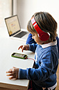 Little boy listening to the music of his smartphone with headphones while his brother using laptop - VABF01055