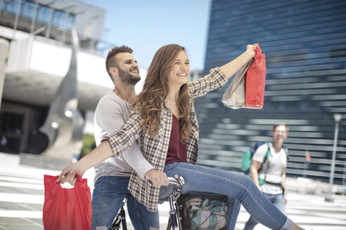 Happy young couple having fun in the city riding bicycle with shopping bags - ZEF12481