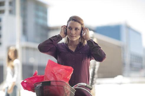 Young woman wearing headphones on bicycle - ZEF12484