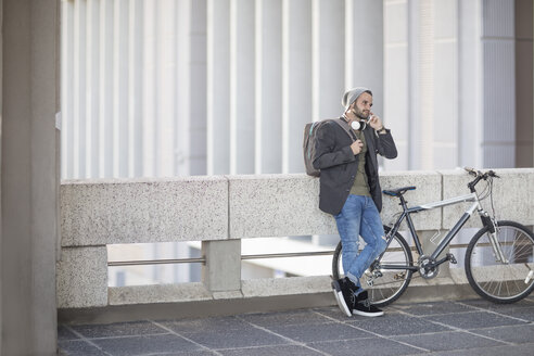 Young man on cell phone next to bicycle - ZEF12490