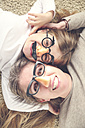 Portrait of mother and daughter lying on the carpet wearing funny glasses with plastic nose - RTBF00602