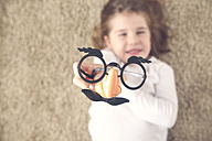 Little girl lying on the carpet holding funny glasses with plastic nose, close-up - RTBF00608