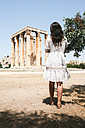 Greece, Athens, woman visiting the Olympieion with the Acropolis in the background - GEMF01414