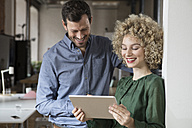 Smiling man and woman looking at tablet in office - RBF05581