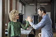 Happy man and woman high fiving in office - RBF05587