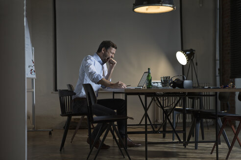 Exhausted businessman working late in office - RBF05611