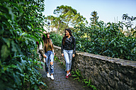 Two smiling young women walking on a path with plants - KIJF01110