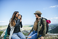 Two happy young women on a trip taking a photo - KIJF01113
