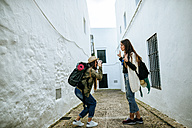 Young traveling women taking photos in a town - KIJF01119