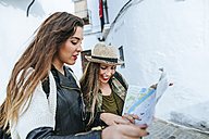 Two young women in a town looking at a map - KIJF01125
