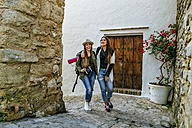 Two smiling young women on a trip walking in a town - KIJF01128