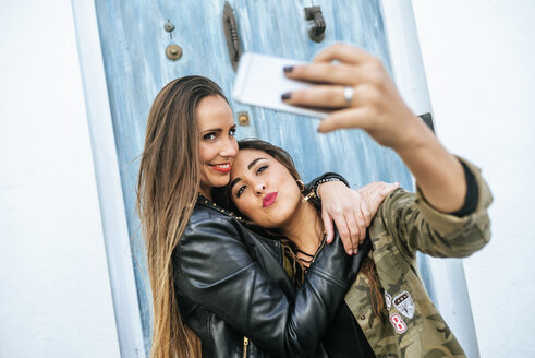 Two happy young women taking a selfie with a smart phone - KIJF01131