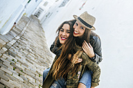 Happy young woman giving friend a piggyback ride - KIJF01137