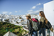 Spain, Andalusia, Vejer de la Frontera, two young women looking from balcony on the town - KIJF01140