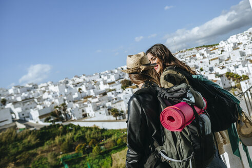 Spain, Andalusia, Vejer de la Frontera, two young women looking with the town in background - KIJF01143