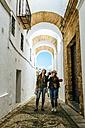 Spain, Andalusia, Vejer de la Frontera, two young women taking a photo in the alley El Callejon de las Monjas - KIJF01149