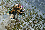 Two happy young women taking a selfie with a camera - KIJF01161