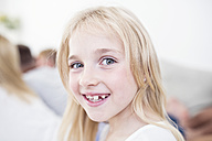 Portait of smiling blond girl with family in background - WESTF22547