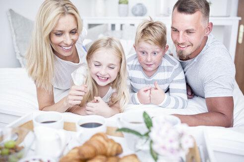 Happy family having breakfast in bed - WESTF22565