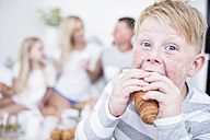 Portrait of boy biting into croissant with family in background - WESTF22568