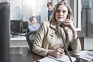 Young woman at desk in office on the phone - ZEF12493