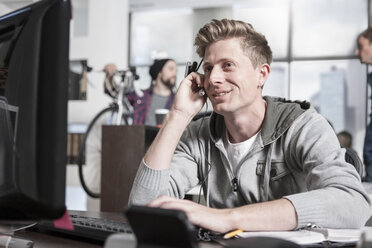 Young man at desk in office wearing a headset - ZEF12496