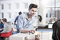 Young man in office smiling at female colleague - ZEF12505