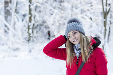 Portrait of smiling young woman in snow-covered nature - JUNF00777